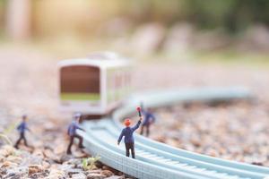 equipe ferroviária em miniatura trabalhando em uma ferrovia, conceito de viagens de trem