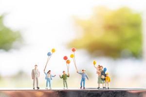 família em miniatura com balões, relações familiares felizes e conceito de lazer despreocupado foto