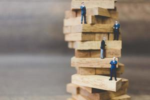 empresários em miniatura em cima de blocos de madeira