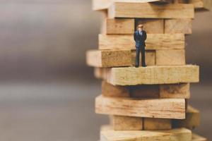 empresário em miniatura em cima de blocos de madeira