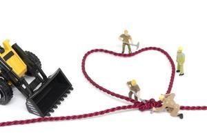 trabalhadores em miniatura construindo uma corda em forma de coração em um fundo branco
