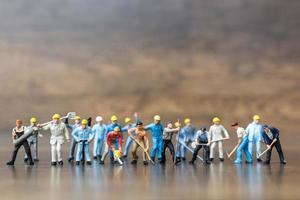 grupo em miniatura de trabalhadores segurando ferramentas em um fundo de madeira foto