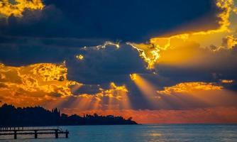paisagem marinha com um pôr do sol laranja e nublado foto