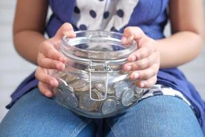 garota segurando o frasco de moedas de perto foto