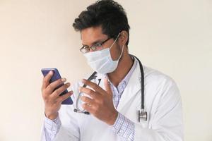 jovem médico falando para câmera de telefone inteligente em chat de vídeo