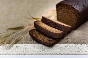 pão preto integral fatiado na mesa foto