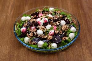 salada de rúcula na mesa de madeira foto