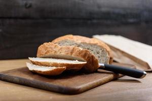 pão de grãos na tábua de madeira foto