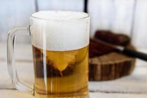 cerveja e pastrami na mesa de madeira