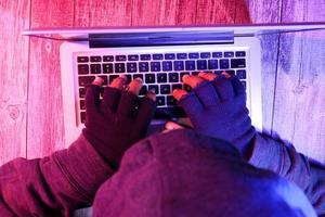 mão de hacker roubando dados de laptop foto