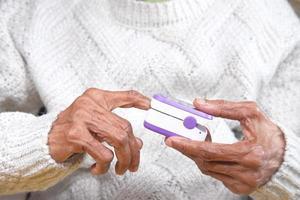 mulher idosa usando oxímetro de pulso foto