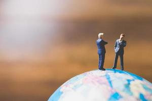 empresários em miniatura em um mapa-múndi com um fundo marrom