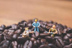 pessoas em miniatura trabalhando em grãos de café torrados