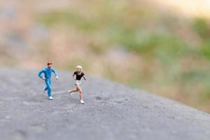 pessoas em miniatura correndo em um conceito de rocha, saúde e estilo de vida foto