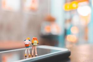 turista mochileiro em miniatura em um smartphone, conceito de viagens foto