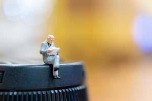 empresário em miniatura sentado com um fundo colorido bokeh foto