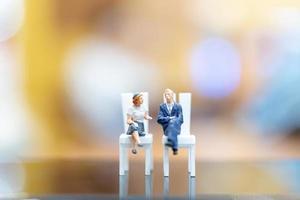 Empresários em miniatura sentados em cadeiras com um fundo colorido bokeh