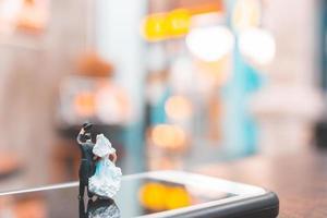 casal em miniatura parado em um smartphone, conceito de amor foto