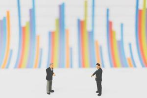 empresários em miniatura sobre um fundo de gráfico
