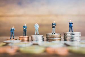 Empresários em miniatura com um fundo de madeira ganhando dinheiro