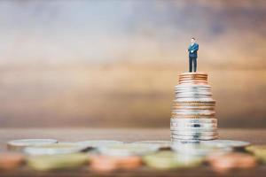 empresário em miniatura com dinheiro e fundo de madeira
