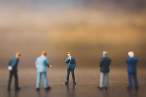 Empresários em miniatura em pé sobre um fundo de madeira