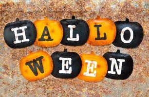 decorações de halloween, abóboras pretas e laranja em fundo de textura de manchas de ferrugem