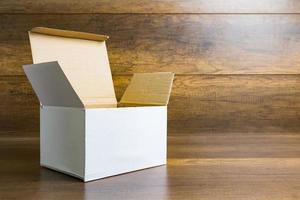 caixa de papel branco sobre um fundo de mesa de madeira foto