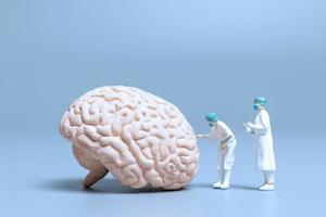 médicos em miniatura verificando e analisando um cérebro em busca de sinais da doença de Alzheimer e demência, ciência e conceito de medicina