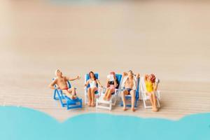 pessoas em miniatura tomando banho de sol na praia, conceito de verão foto