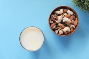 muitas nozes misturadas em uma tigela com um copo de leite no fundo azul foto