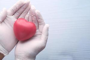 mão do médico com o coração em fundo neutro foto