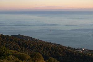 vista aérea de montanhas e cidade distante ao lado de corpo d'água em sochi, rússia foto