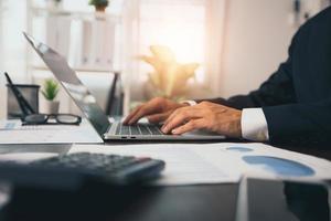 close-up de mãos de empresário digitando e trabalhando no laptop foto