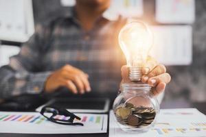 empresário segurando uma lâmpada em um copo de moedas com papéis financeiros foto