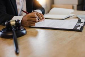 mão do empresário assinando contrato com o martelo da justiça na mesa