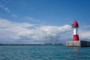 vista do mar com um veleiro vintage e um farol com um céu azul nublado em sochi, na Rússia foto