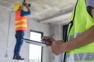 trabalhador inspetor trabalhando e verificando no papel, inspecionando a construção na sala e na casa foto