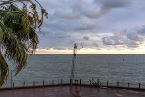 passeio vazio com vista para o mar ao lado de uma palmeira e um corpo de água em sochi, rússia foto