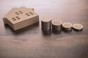 modelo de pequena casa de madeira na mesa com moedas foto
