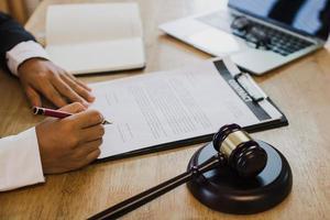 mão do empresário assinando um contrato com a justiça hummer na mesa