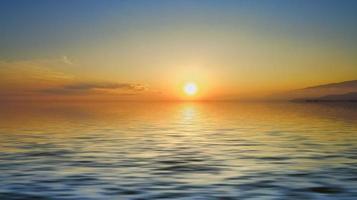 pôr do sol nublado colorido sobre a massa de água foto