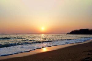 ondas quebrando em uma praia com pôr do sol nublado laranja sobre as montanhas foto