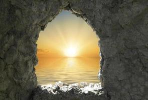 pôr do sol laranja sobre um corpo d'água visto por uma janela em uma parede de pedra foto