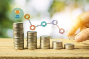 negócio econômico de capital financeiro, mão colocando moedas de dinheiro empilhadas na mesa de madeira foto