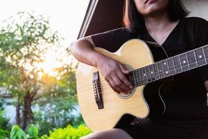 mulher tocando violão lá fora