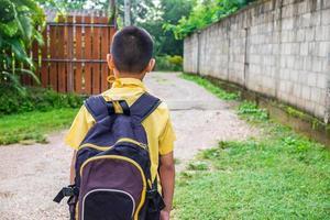menino em uma camisa amarela com uma mochila