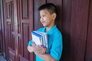 menino segurando livros