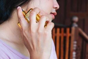close-up de mulher espalhando perfume no pescoço foto