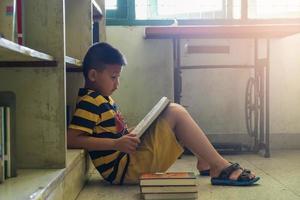 menino lendo um livro em uma biblioteca